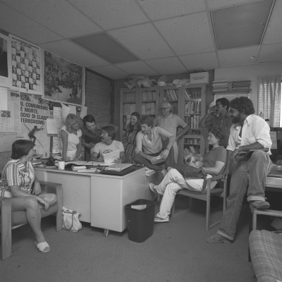 Vintage photo of students reading a newspaper in an office.