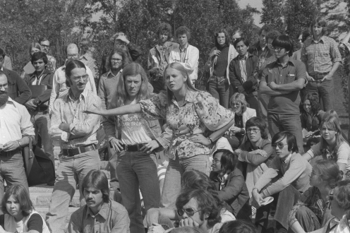 Vintage photo of a student making a statement among a group of people.
