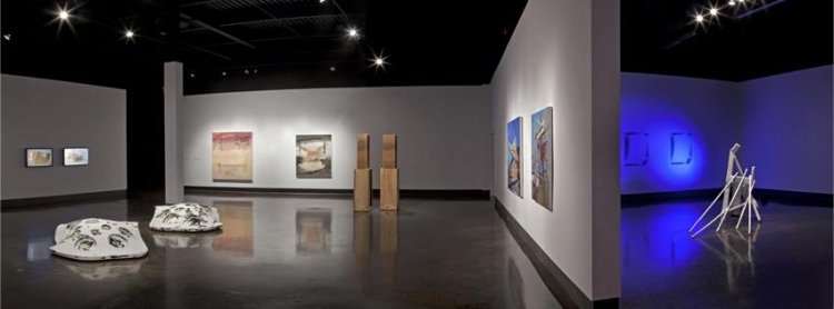 Gallery space with artwork on walls and floor