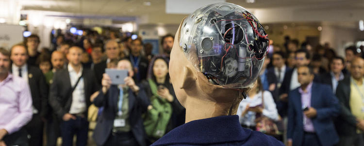 back of robot's head facing large crowd