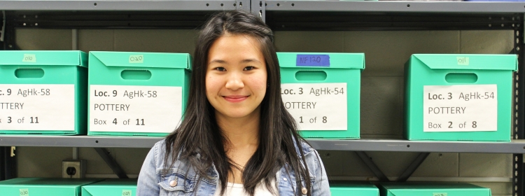 female student smiles in front of boxes labelled Pottery