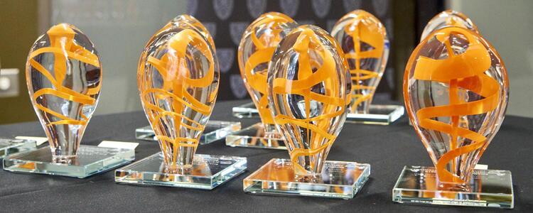 Row of glass sculptures with orange swirl in each