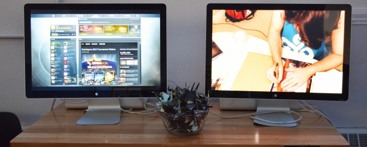 two computer monitors with gaming images and origami