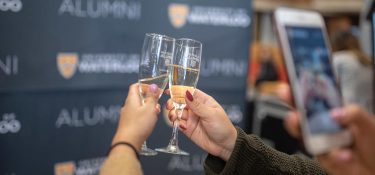 Two hands toasting with champagne glasses with Alumni banner behind