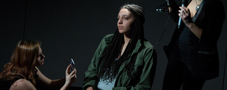 student actors with one sitting and two others recording her with devices