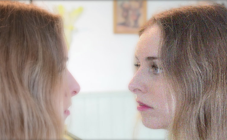Video still showing a woman looking at a pixelated version of herself in a mirror