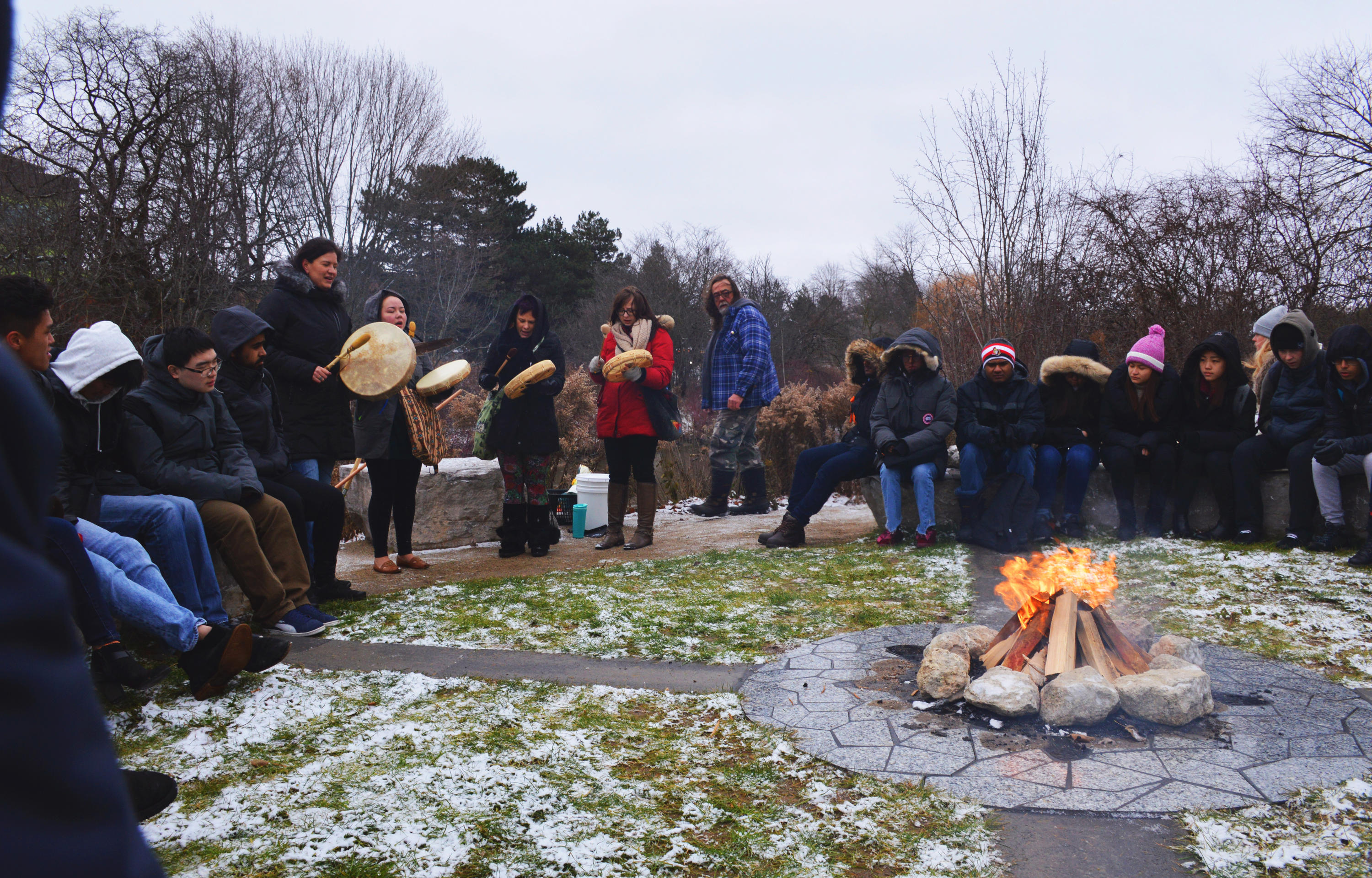 people gathered around ceremonial fire with drummers and singers