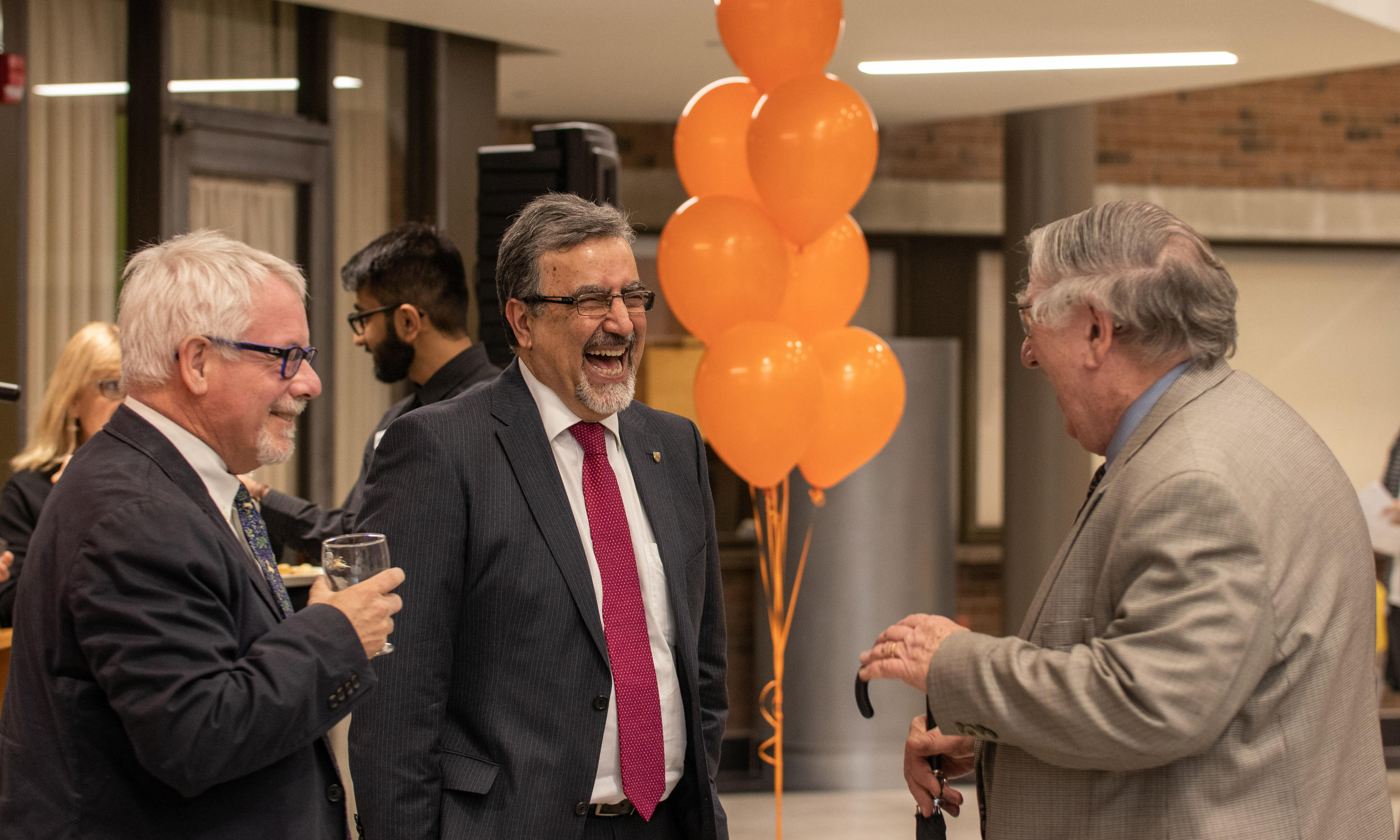 dean of arts, president and provost laugh together