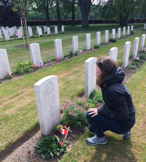 student kneels by grave