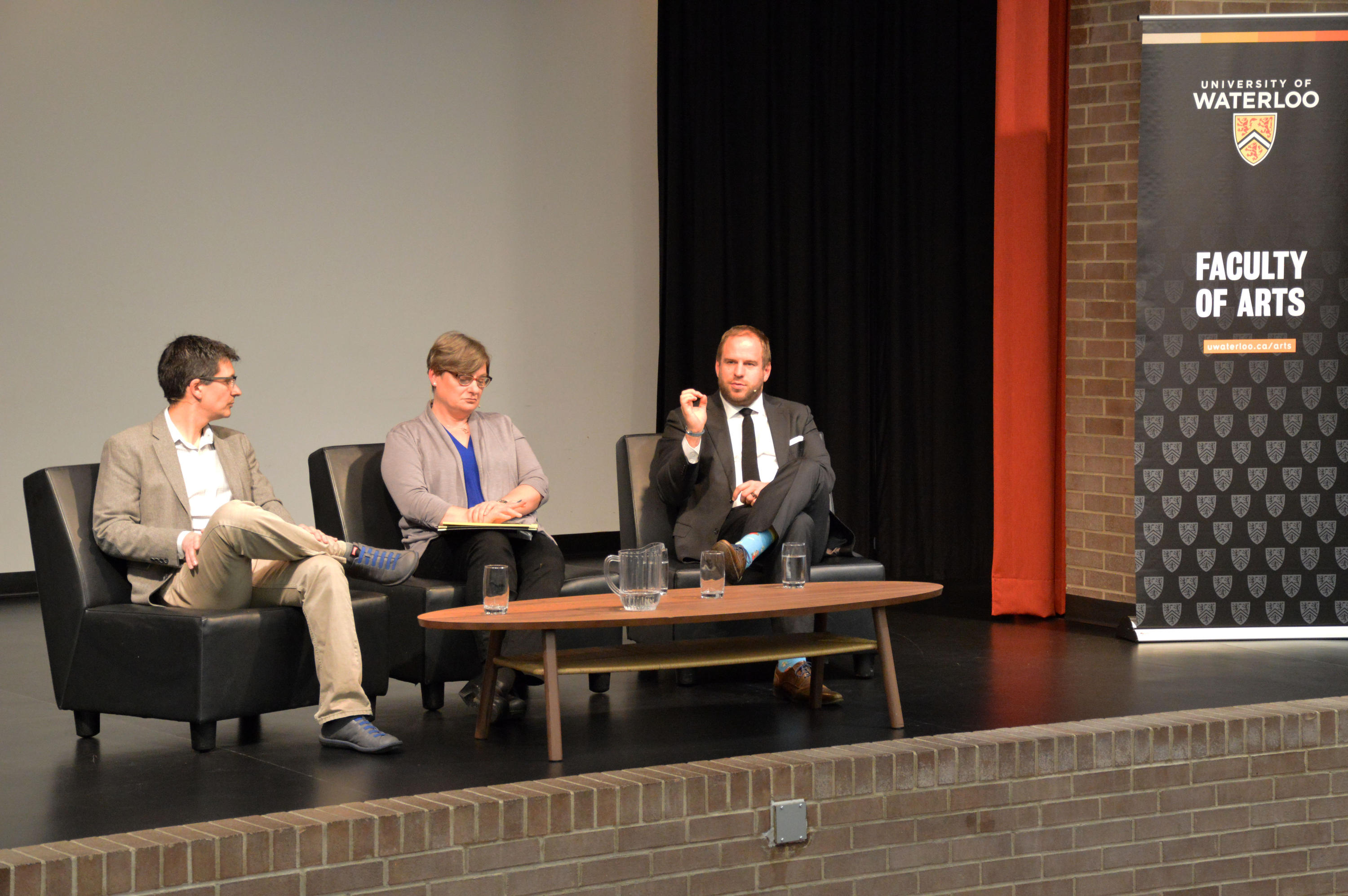 three professors in chairs on stage at event