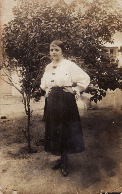 old fashion image of little girl standing by a tree