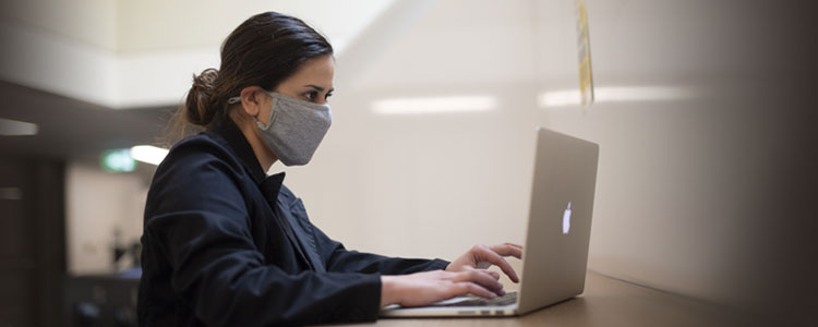 Grad student working on laptop, wearing a cloth mask