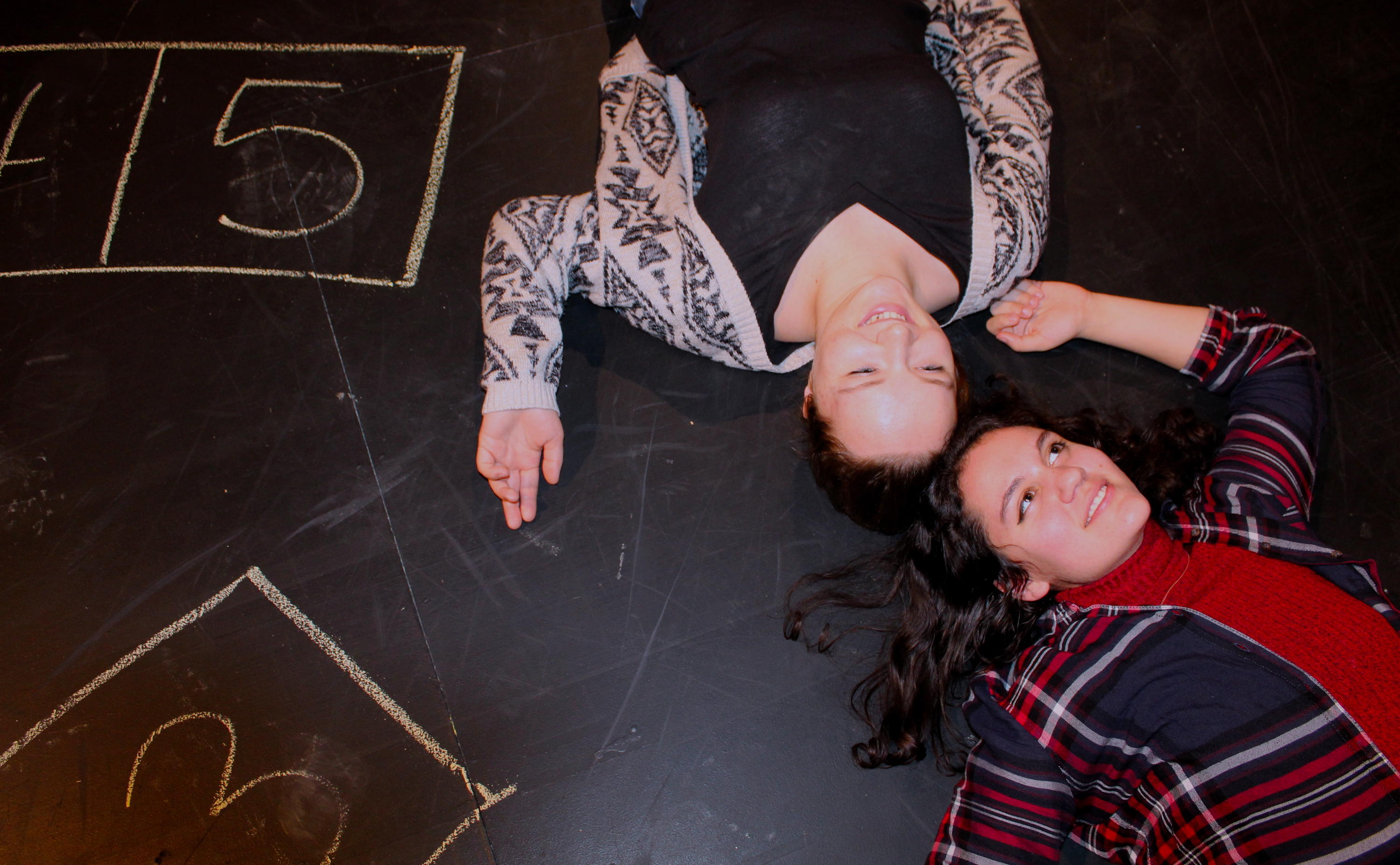 two actors lying on stage with chalked numbers