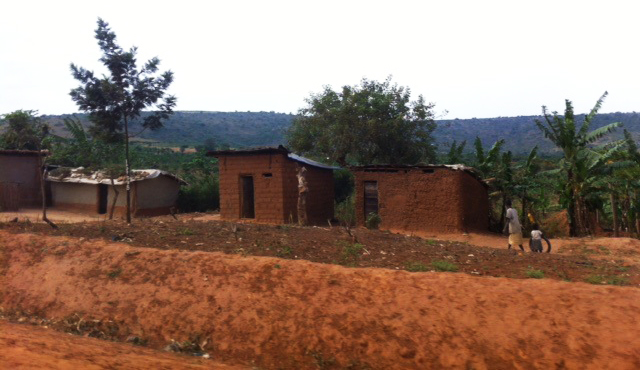 Ugandan dirt field and huts in background