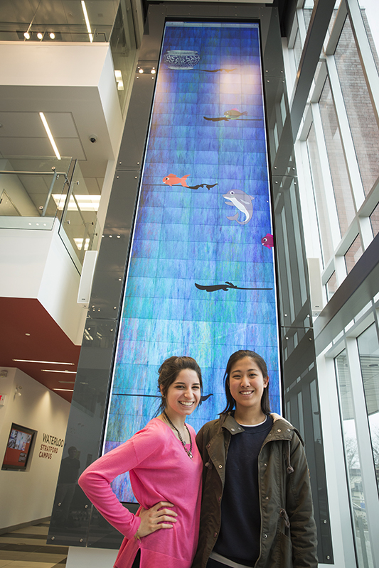 two students stand in front of digital wall