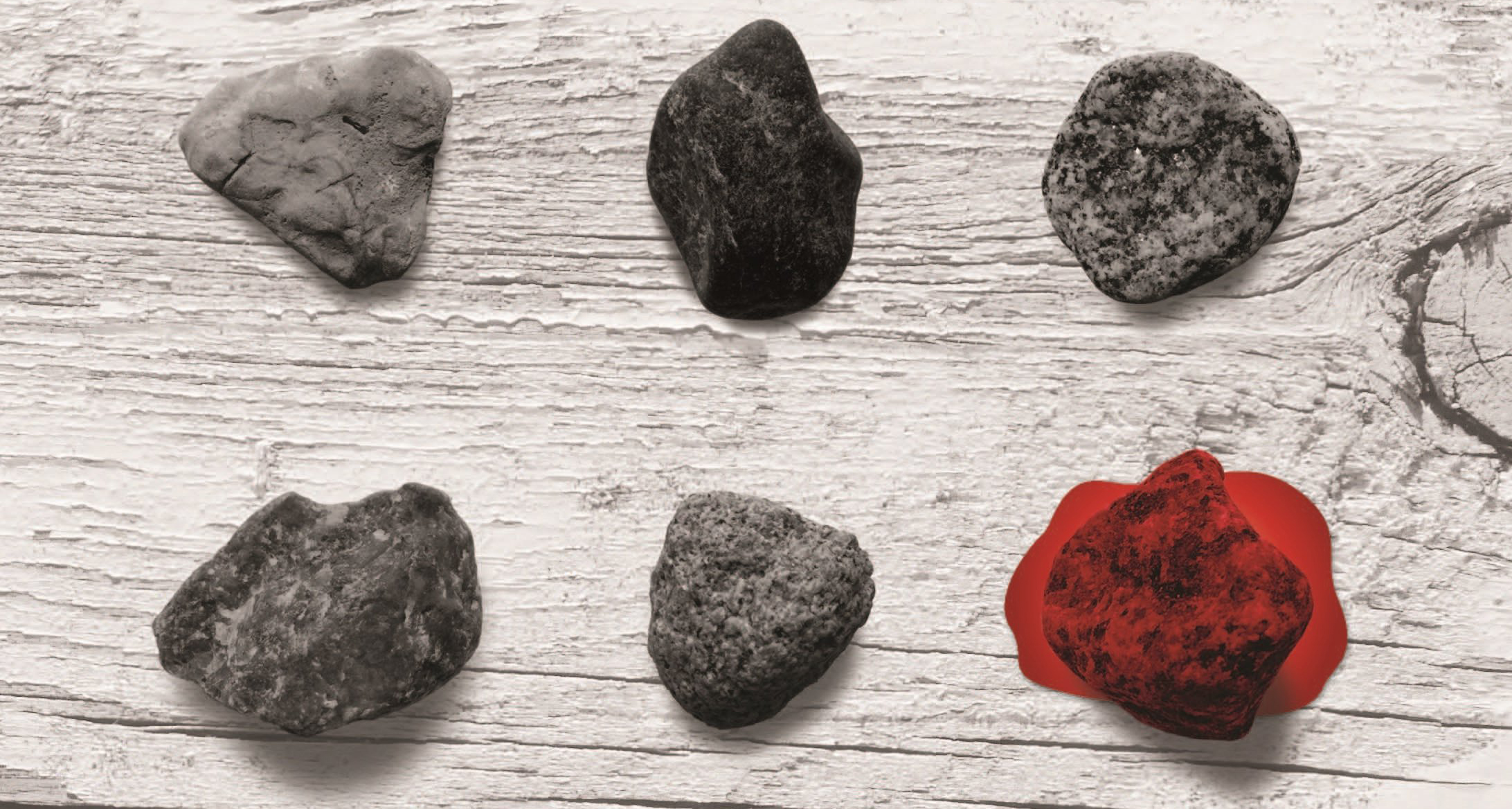 stones against wood surface, with one stone in blood red
