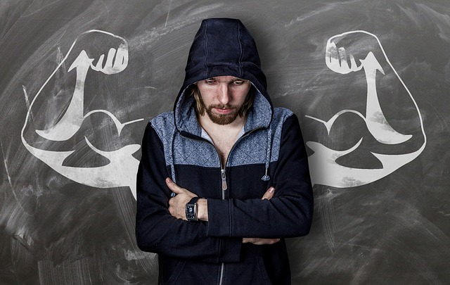 man looking down set against drawing of a muscular set of arms