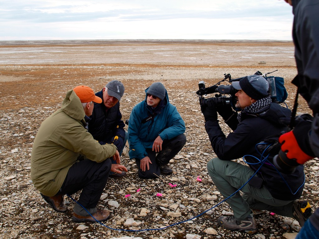 men being filmed by camera man on arctic tundra