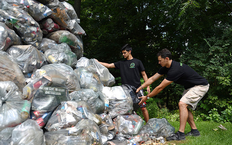Dillon Mendes and Sam Demma build a tall pile of garbage bags
