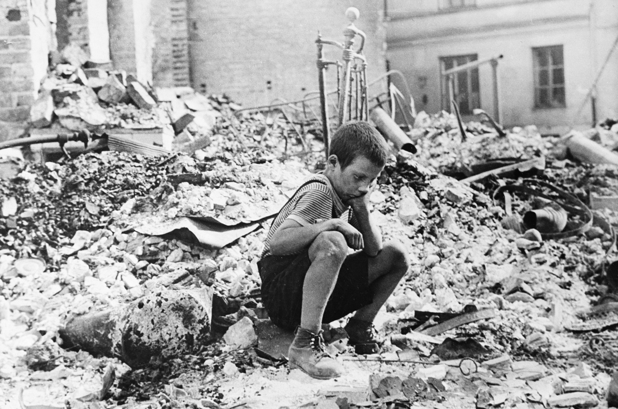 Polish boy sits sadly in ruins of Warsaw in 1939