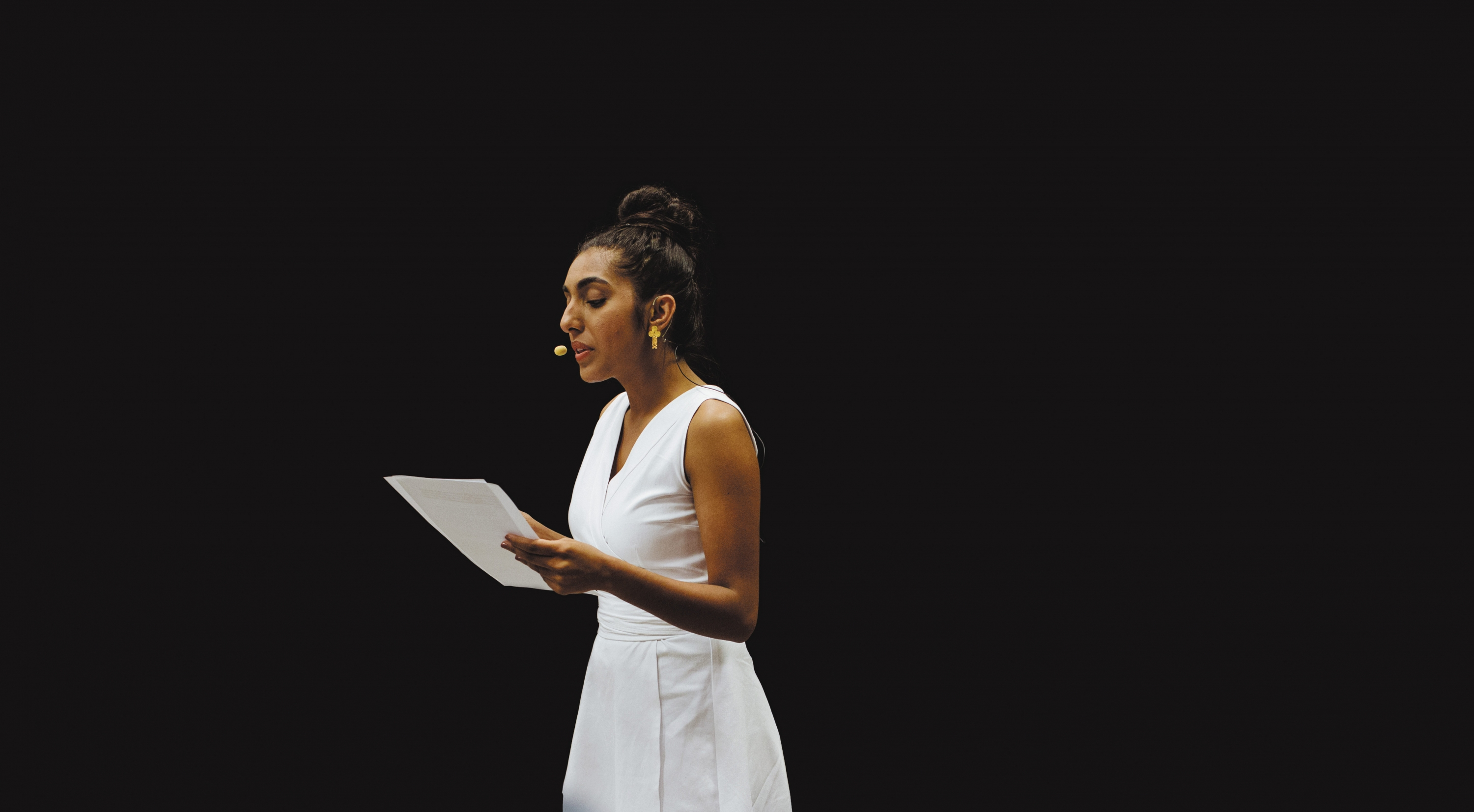 Rupi Kaur in white dress reading from script