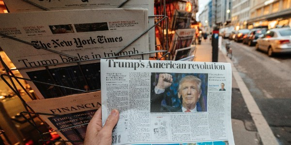 person's hand holding paper with headlines about Trump