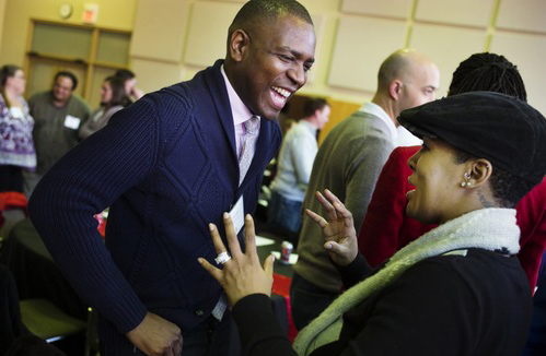 Vershawn Young speaking with person at gathering