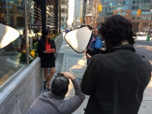 Photographers capturing Priya glancing down at her tablet during photoshoot.