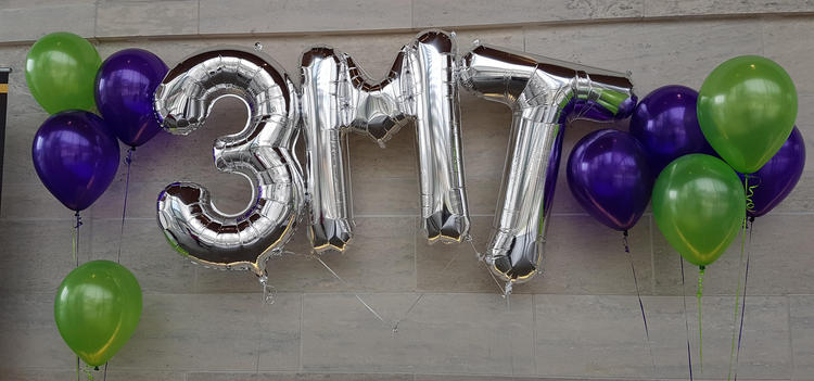Purple and green helium balloons with silver 3MT in the middle
