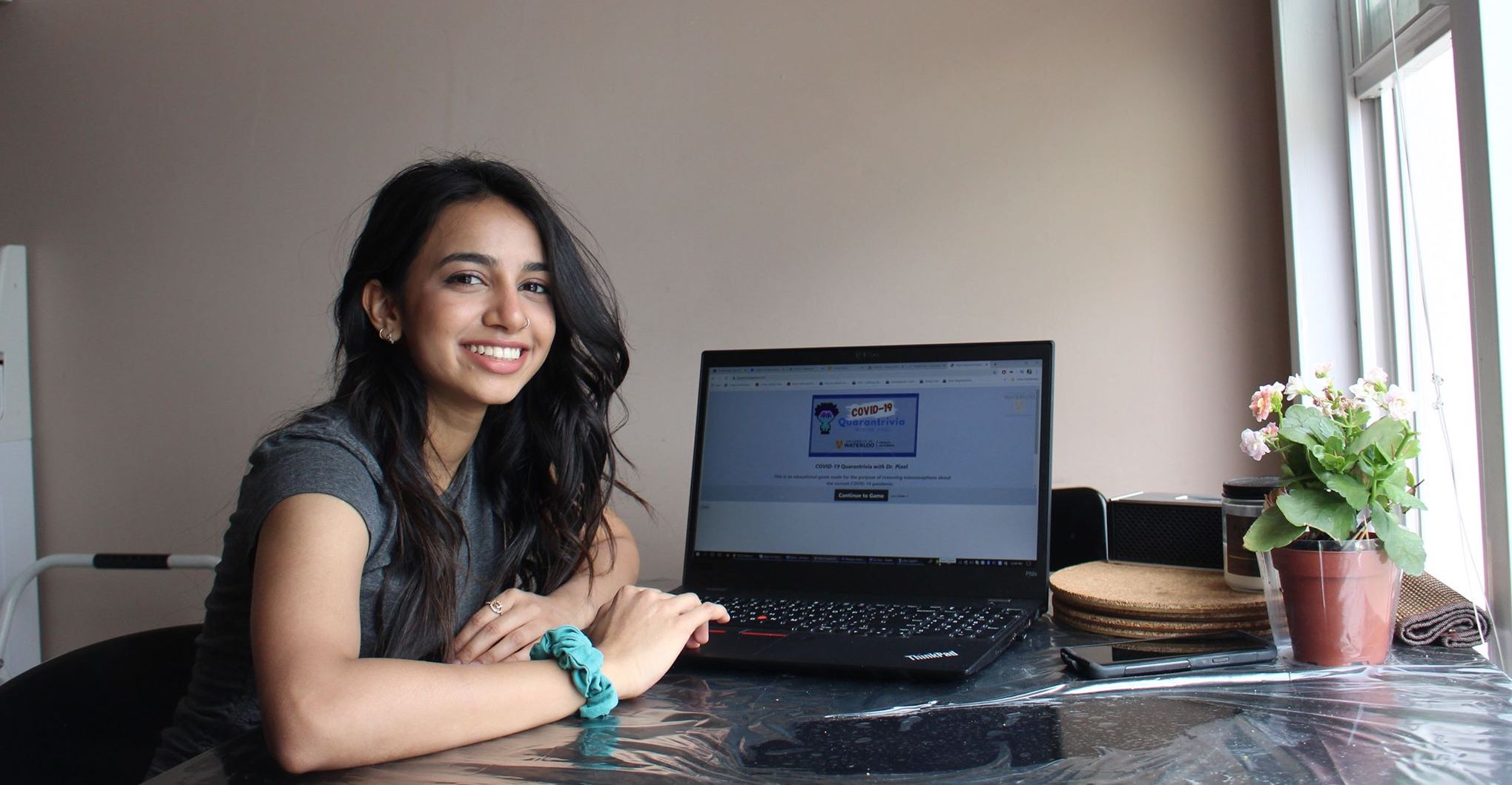 Ridhi Patel sits next to laptop with covid trivia game on the screen.