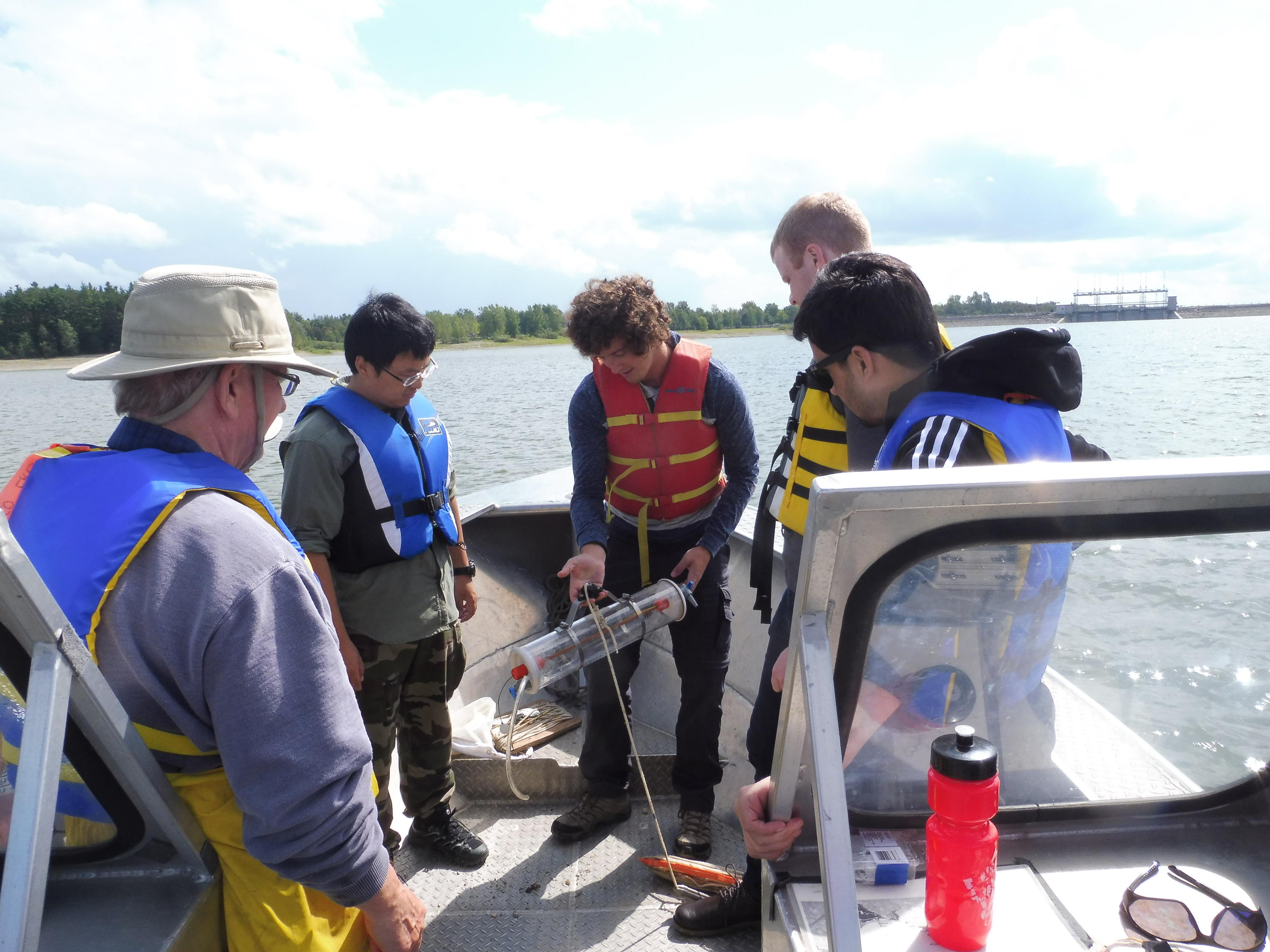 Water Collaborative Program students sampling on the Grand River in a boat.
