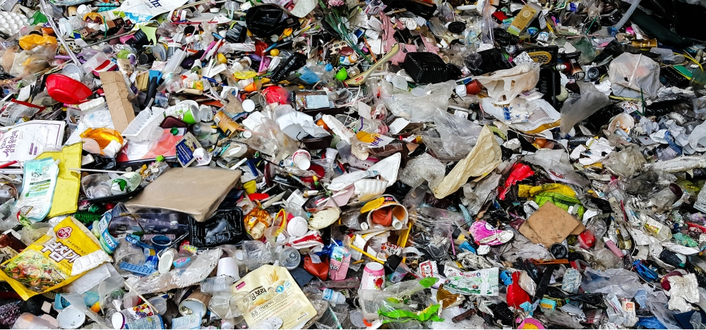 Pile of garbage, paper and plastic in landfill.