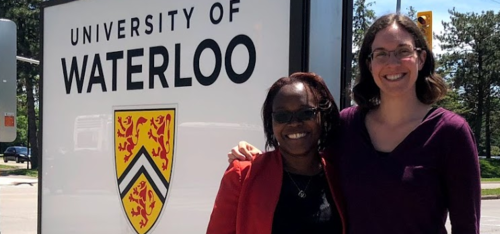 Prof. Laura Hug and female colleague stand by University of Waterloo sign.