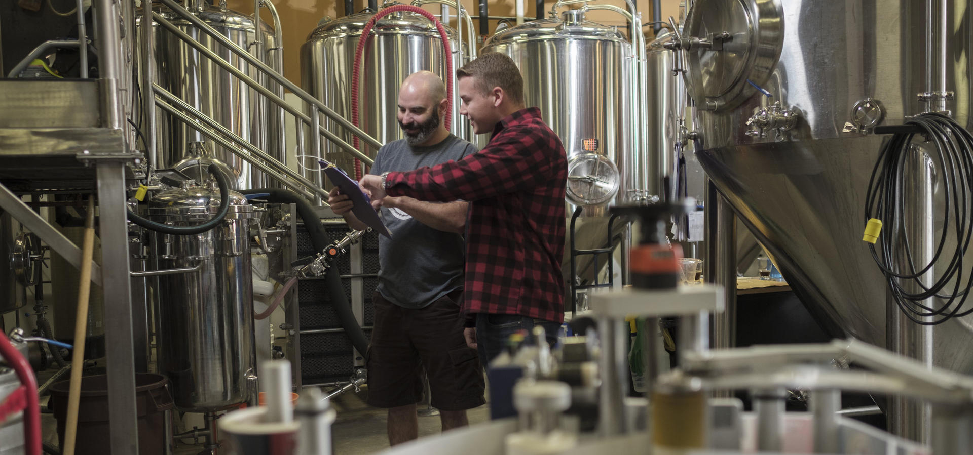 Science alumn Steve Innocente and co-op student Tyler Ball discussing content on a clipboard in the brewery