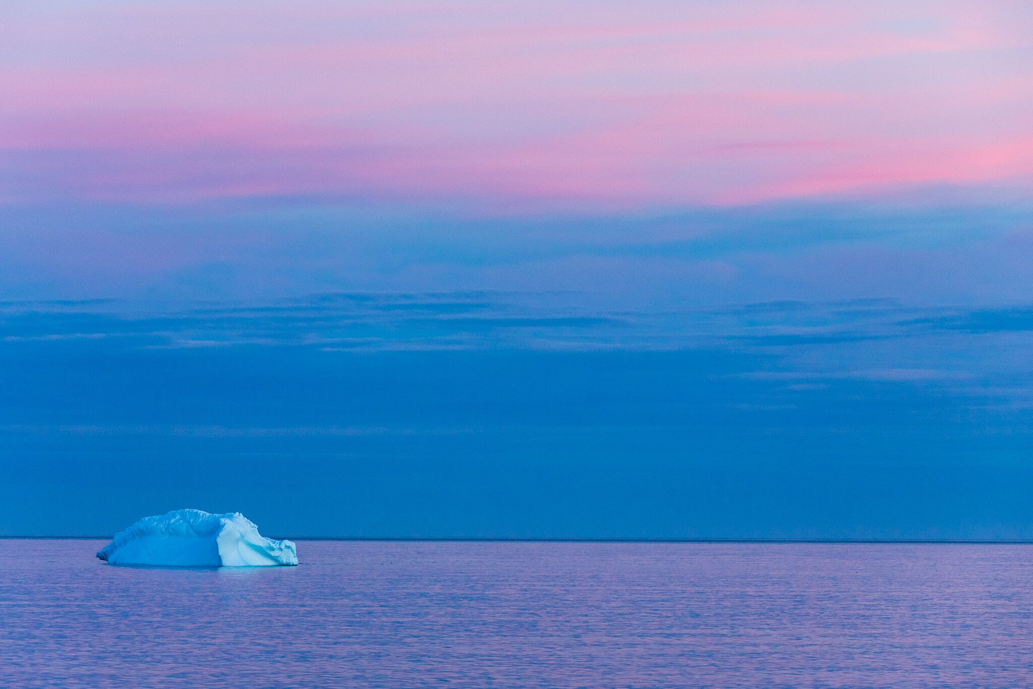 Solitary iceberg on the ocean during sunset. The sky and ocean are blue and purple sunset colours