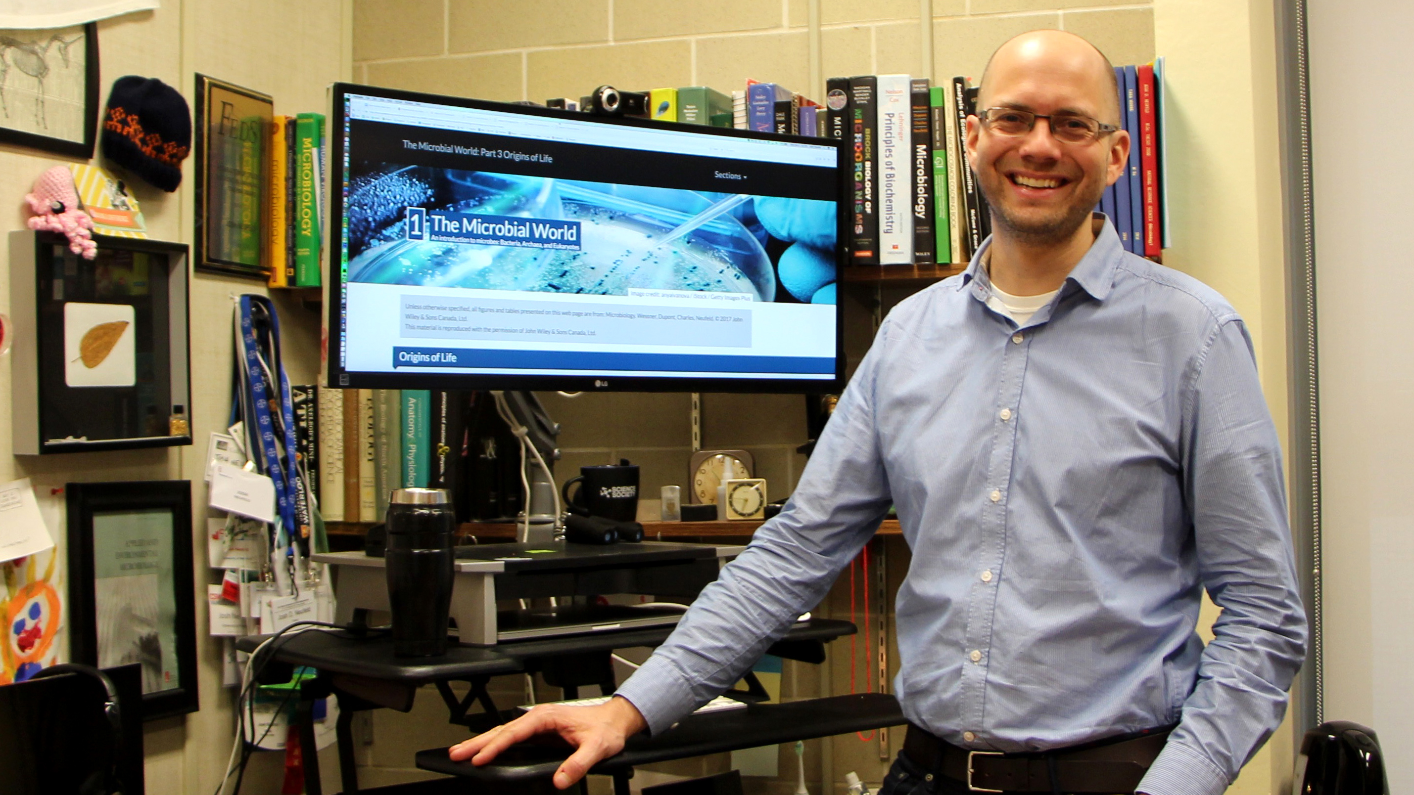 Josh Neufeld standing in front of a CEL course banner.