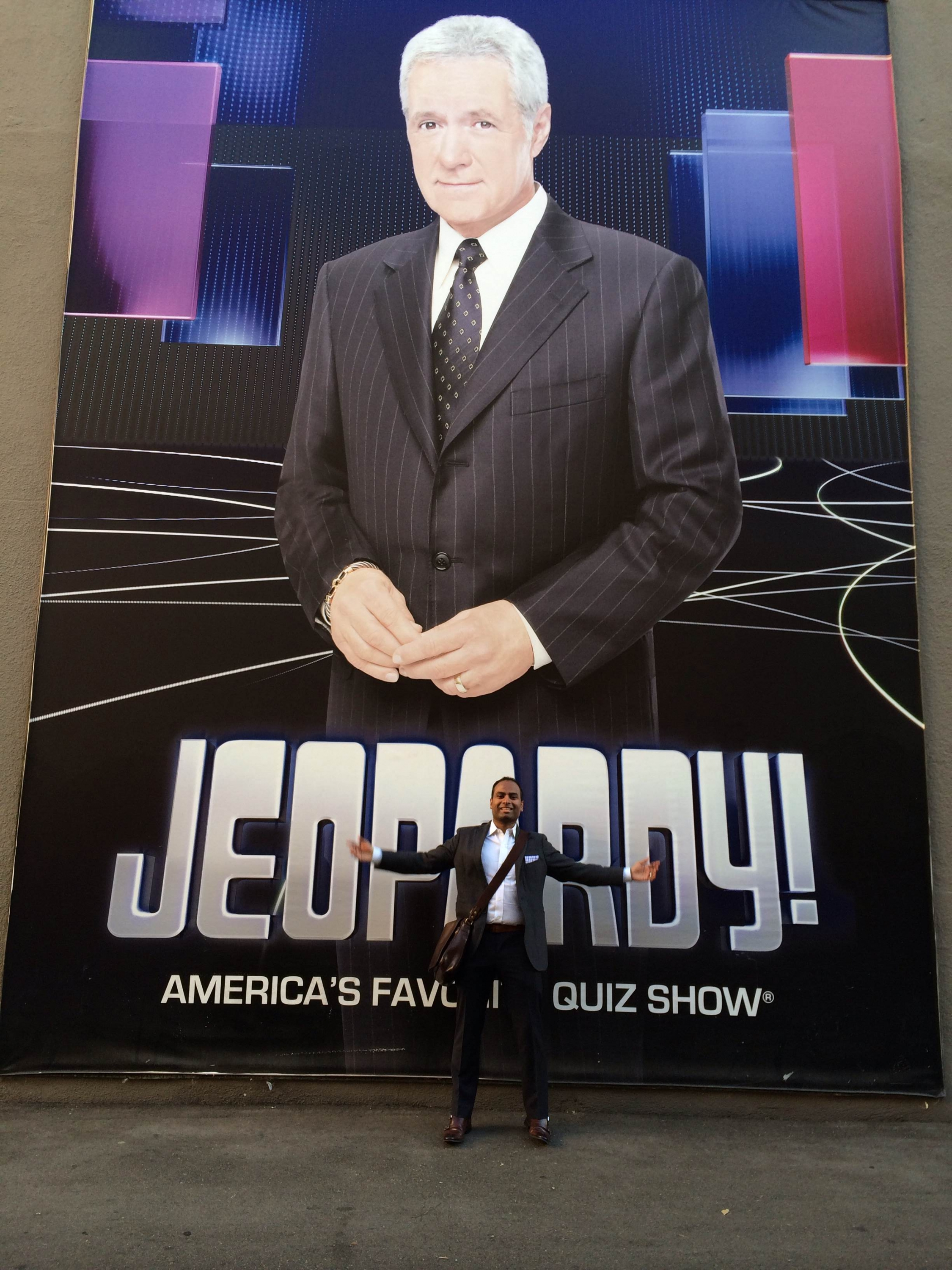 Dinu Nesan standing in front of Jeopardy! poster.