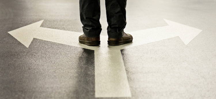 Stock image of feet standing on the intersection of an arrow pointing right and an arrow pointing left.