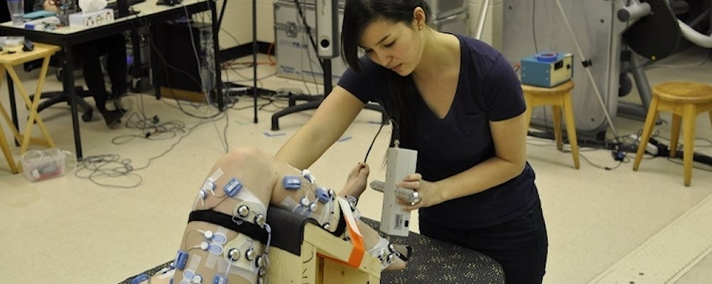 Lab member applies force to subject's foot to test ankle flexibility.