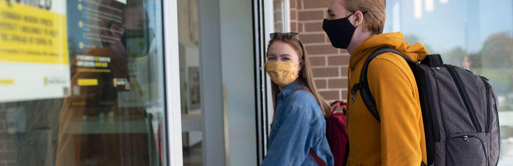 Two masked students entering a building