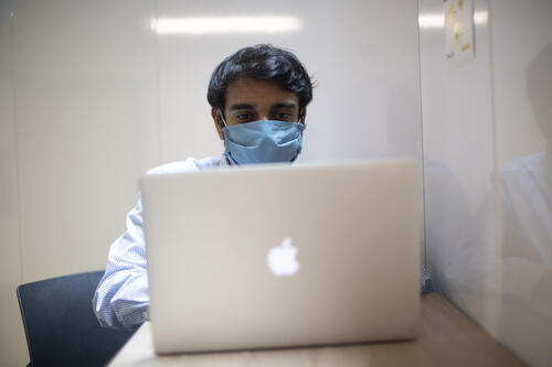 Person using a computer wearing a face mask