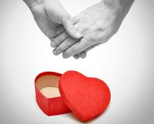 hands holding over a heart shaped box