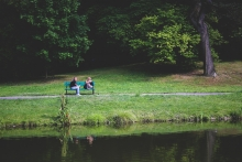 Two people talking on a bench in front of a lake