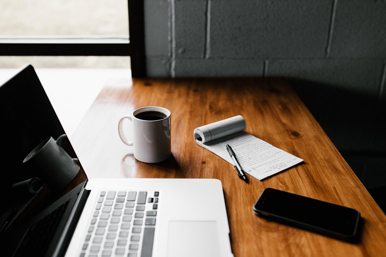 Laptop, ceramic mug, notebook and phone on desk