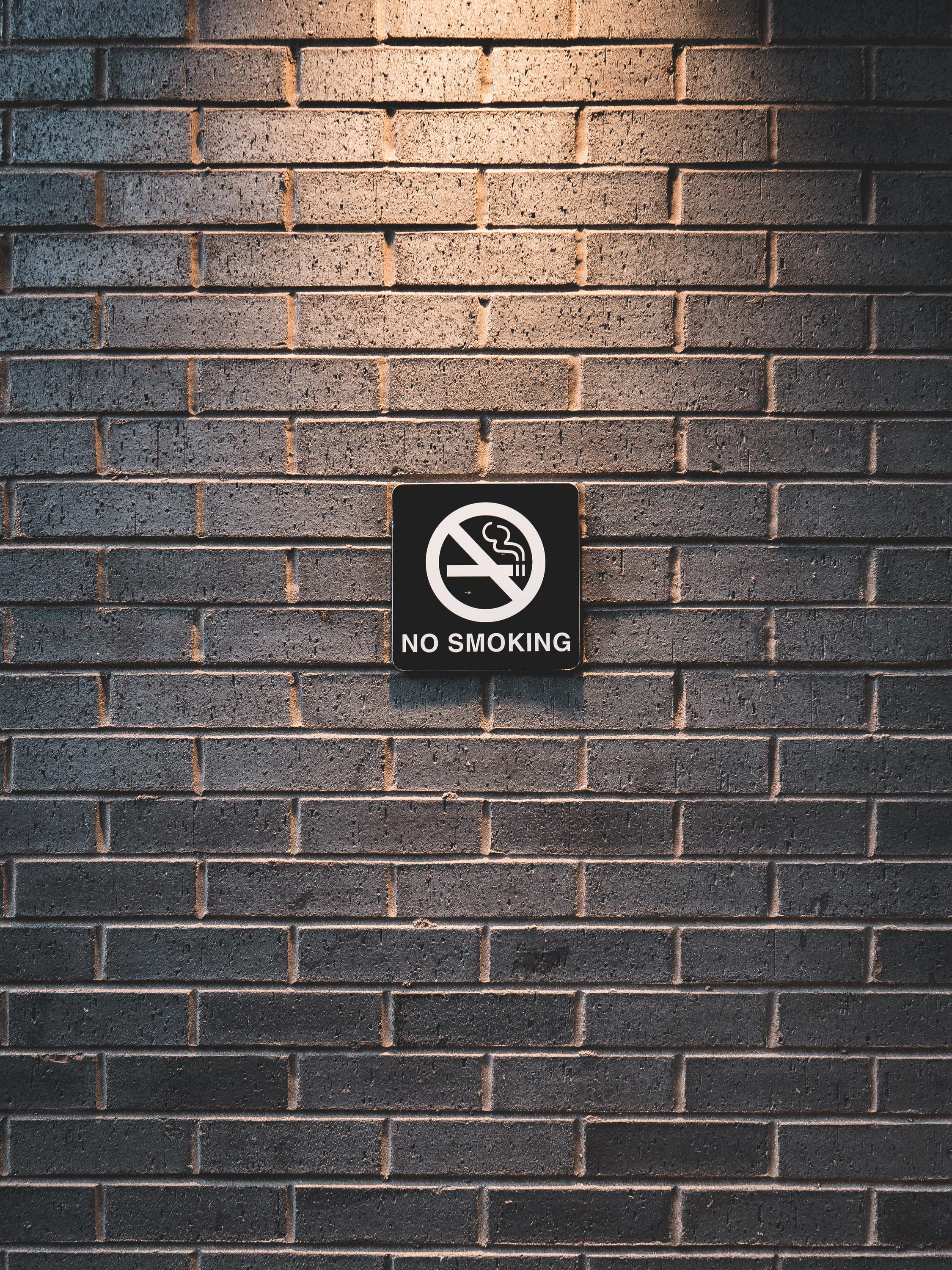 "Black ""no smoking"" sign on a grey brick wall"