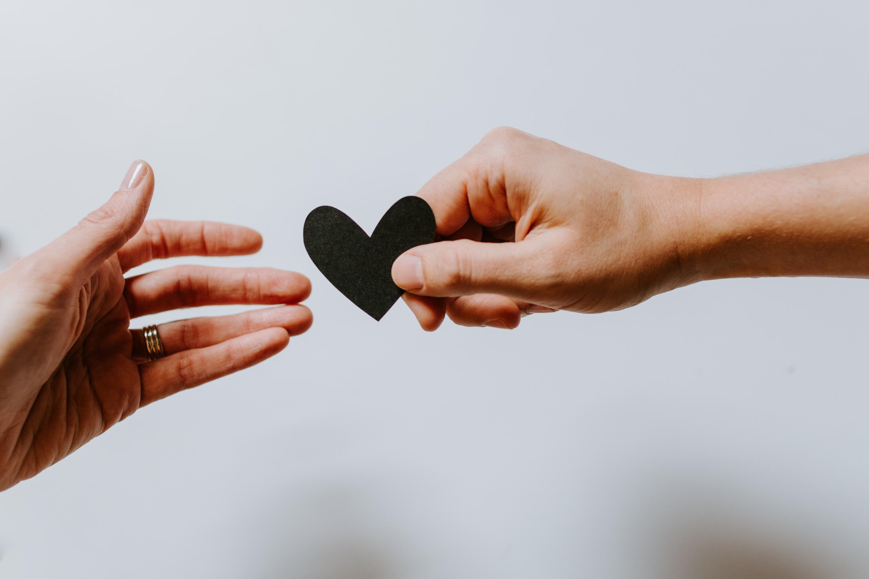 Hands passing heart cutout