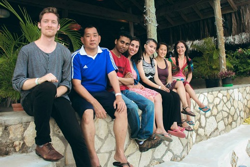 Seven graduate students sitting on a stone ledge smiling at camera in Jamaica