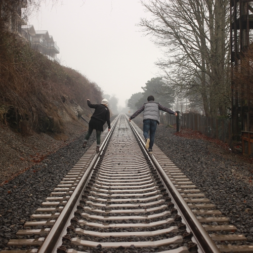 two people balancing on railroad track\