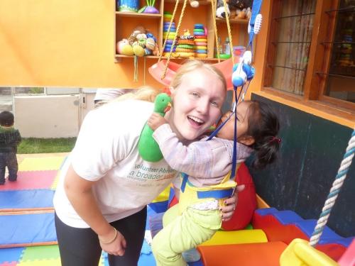 a teenage girl volunteering in an orphanage in Peru