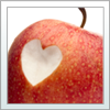 Healthy Populations. A photo of an apple with a heart-shape cut out.